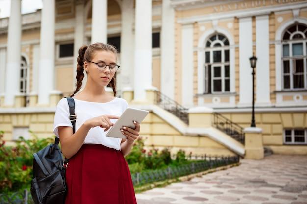 Jonge mooie vrouwelijke student die in glazen tablet in openlucht bekijken.