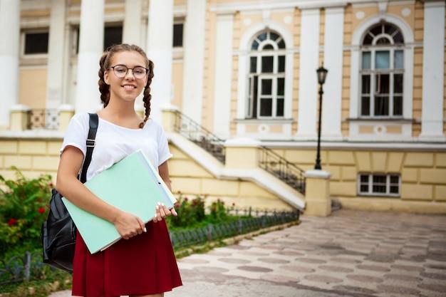 Jonge mooie vrouwelijke student in glazen glimlachen, die omslagen in openlucht houdt.
