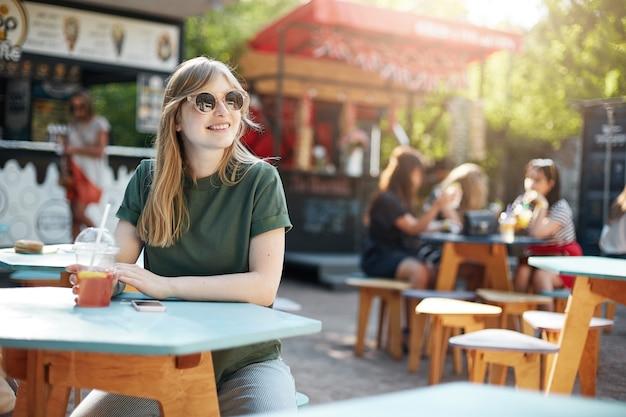 Jonge mooie vrouwelijke student ontspannen van lessen op weekend drinken grapefruit limonade glimlachen