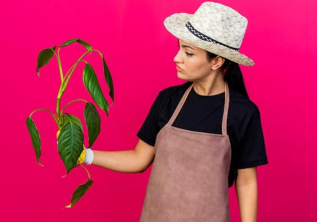 Jonge, mooie vrouwelijke tuinman in rubberen handschoenen, schort en hoed met plant, kijk ernaar met een serieus gezicht