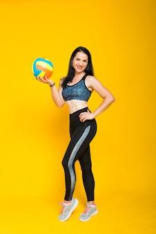 Jonge mooie vrouwelijke volleyballer die op geel in studio wordt geïsoleerd