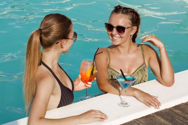 Jonge mooie vrouwelijke vrienden die terwijl het hebben van dranken samen bij het zwembad babbelen