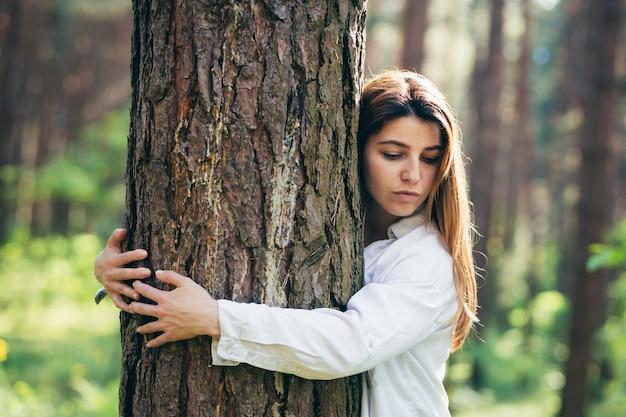 Jonge mooie vrouwelijke vrijwilliger knuffelt een boom met liefde in het bos