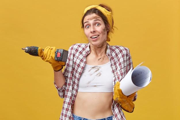 Jonge mooie vrouwelijke werknemer van de onderhoudsdienst die boor en blauwdruk draagt die overhemd en witte bovenkant draagt die twijfelachtige blik heeft die haar schouders ophaalt. mensen, beroep en beroep concept.