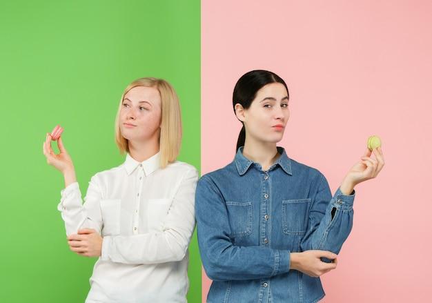 Jonge mooie vrouwen die makaronsgebakje in haar handen houden