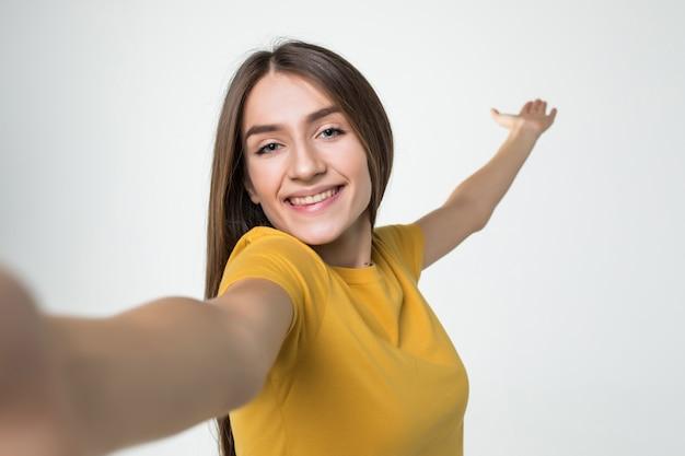 Jonge mooie vrouwen die selfie op celtelefoon nemen die op witte muur wordt geïsoleerd