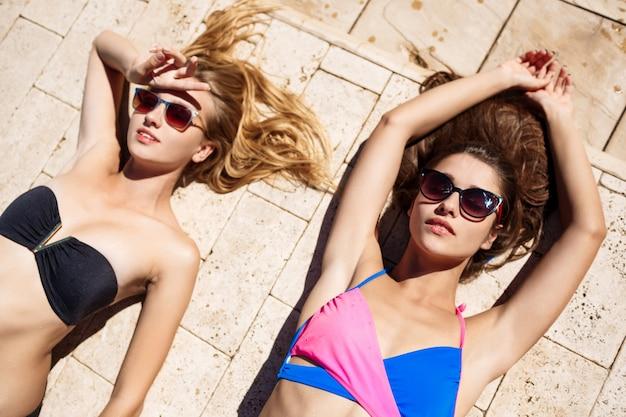 Jonge mooie vrouwen die, zonnebaden glimlachen, die dichtbij zwembad ontspannen.
