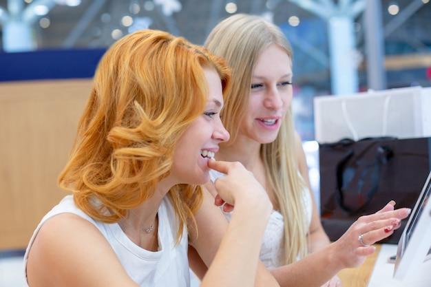 Jonge mooie vrouwen in een reisbureau kiezen een vakantiereis, met behulp van het interactieve scherm.