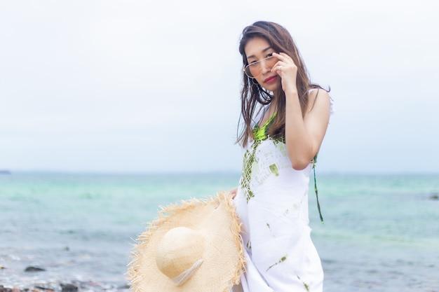 Jonge mooie vrouwen in het wit met strohoed op het strand.