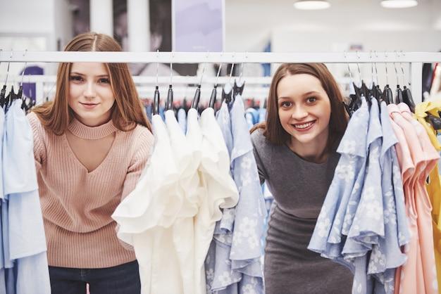 Jonge mooie vrouwen op de wekelijkse kledingmarkt - beste vrienden die vrije tijd delen met plezier en winkelen in de oude stad op een zonnige dag - vriendinnen die genieten van alledaagse momenten