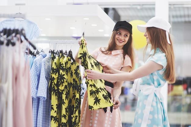 Jonge mooie vrouwen op de wekelijkse kledingmarkt - beste vrienden die vrije tijd delen met plezier en winkelen