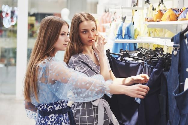 Jonge mooie vrouwen op de wekelijkse stoffenmarkt - beste vrienden die vrije tijd delen die pret hebben en winkelen