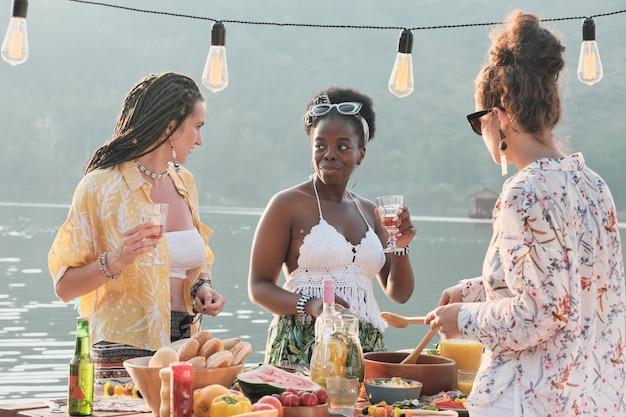 Jonge mooie vrouwen staan in de buurt van de eettafel en praten met elkaar, ze lunchen buiten