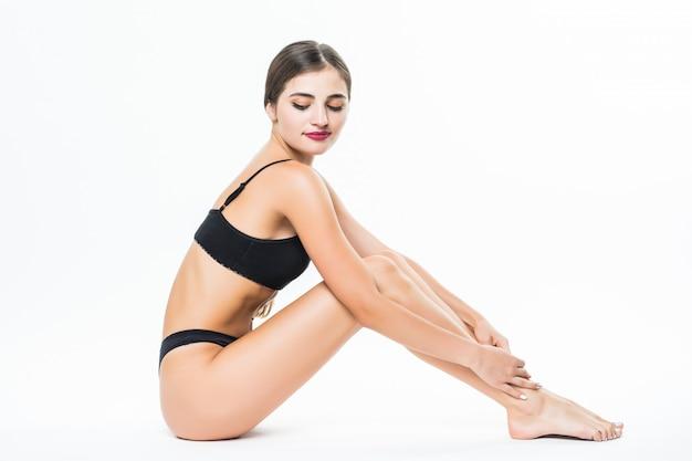 Jonge mooie vrouwen vrouwelijke benen die op witte muur worden geïsoleerd