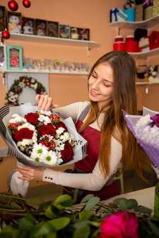 Jonge mooie vrouwenbloemist die een boeket houdt terwijl status bij de box van een bloemwinkel