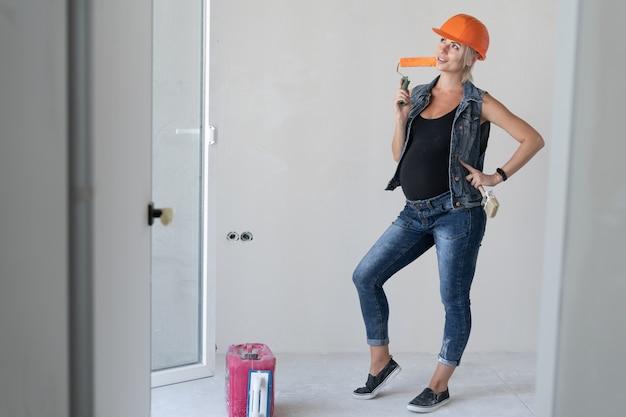 Jonge mooie vrouwenbouwer in een oranje beschermende helm op haar hoofd. zwanger meisje. staat binnenshuis met een verfroller in zijn handen. plaats voor tekst