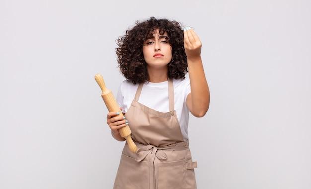 Jonge mooie vrouwenchef-kok die capice of geldgebaar maakt, die u vertelt uw schulden te betalen!