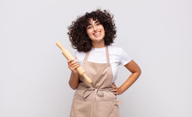 Jonge mooie vrouwenchef-kok die gelukkig met een hand op heup glimlacht en zelfverzekerde, positieve, trotse en vriendelijke houding
