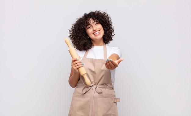 Jonge mooie vrouwenchef-kok die gelukkig met vriendelijke, zelfverzekerde, positieve blik glimlacht, een voorwerp of concept aanbiedt en toont