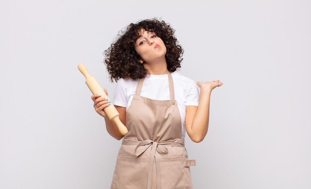 Jonge mooie vrouwenchef-kok die zich in verwarring en verward voelt, twijfelt, weegt of verschillende opties kiest met grappige uitdrukking