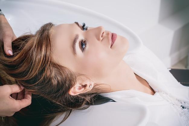 Jonge mooie vrouwencliënt die haarwassen bij een professionele kapper in een close-up van de schoonheidssalon doen