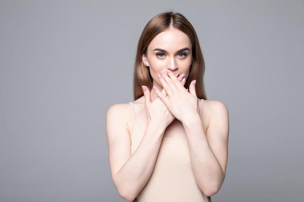 Jonge mooie vrouwendekking met handen haar verraste mond geïsoleerd op witte muur