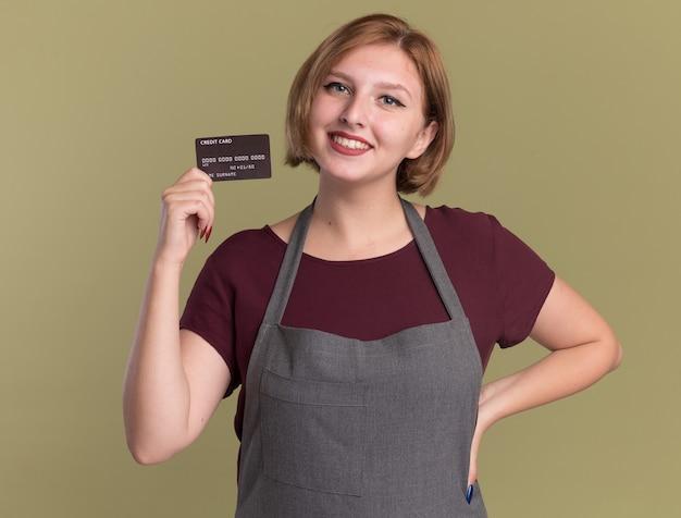 Jonge mooie vrouwenkapper die in de creditcard van de schortholding voorzijde met glimlach op gezicht bekijkt die zich over groene muur bevindt