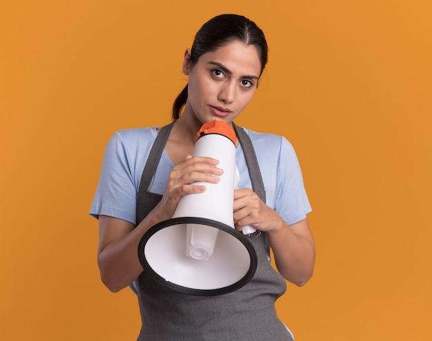 Jonge mooie vrouwenkapper die in de megafoon van de schortholding voorzijde met zelfverzekerde uitdrukking bekijkt die zich over oranje muur bevindt