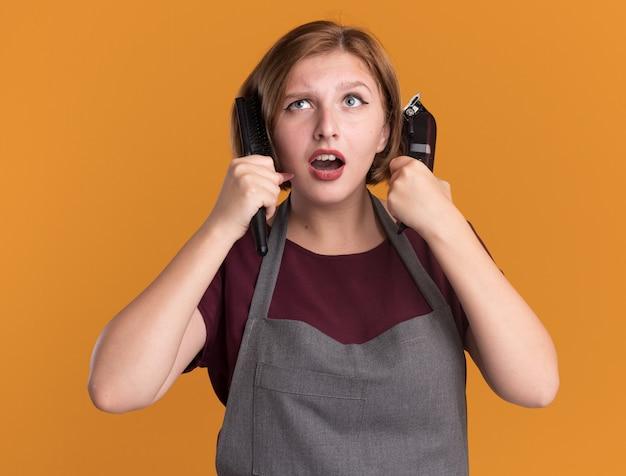 Jonge mooie vrouwenkapper die in de trimmer en de haarborstel van de schortholding omhoog verbaasd status over oranje muur kijken