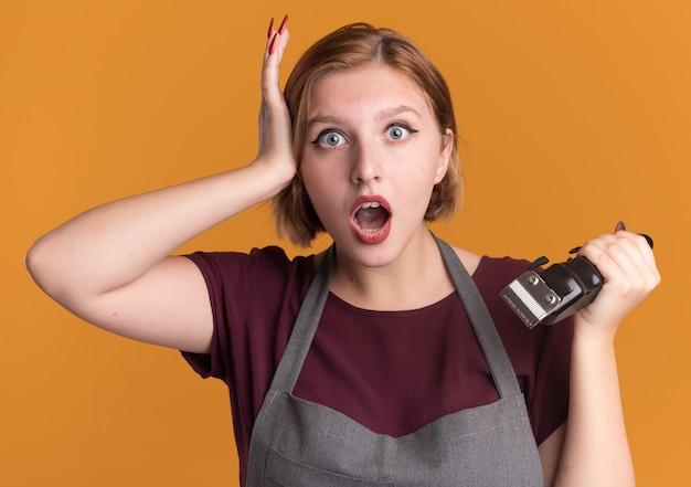Jonge mooie vrouwenkapper die in de trimmer van de schortholding voorzijde bekijkt verrast status over oranje muur