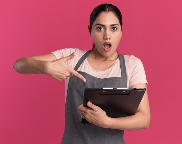 Jonge mooie vrouwenkapper die in het klembord van de schortholding met wijsvinger richt dat wordt verward en verrast status over roze muur