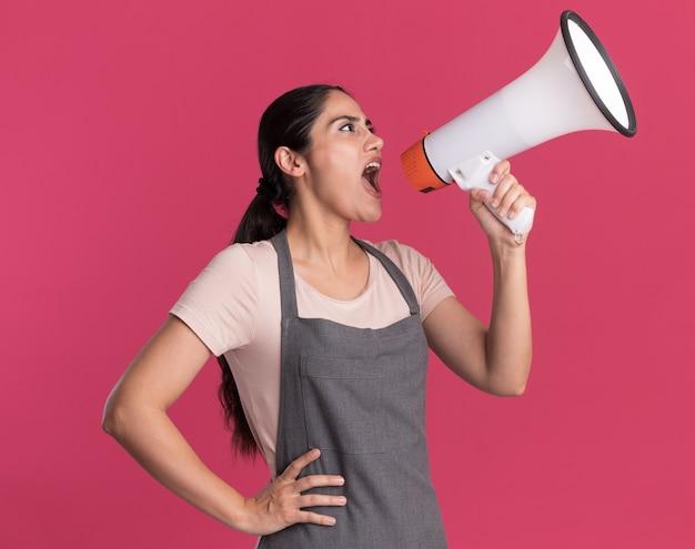 Jonge mooie vrouwenkapper die in schort aan megafoon schreeuwt die zich over roze muur bevindt