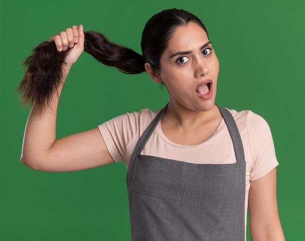 Jonge mooie vrouwenkapper die in schort haar staart houdt die verbaasd status over groene muur kijkt