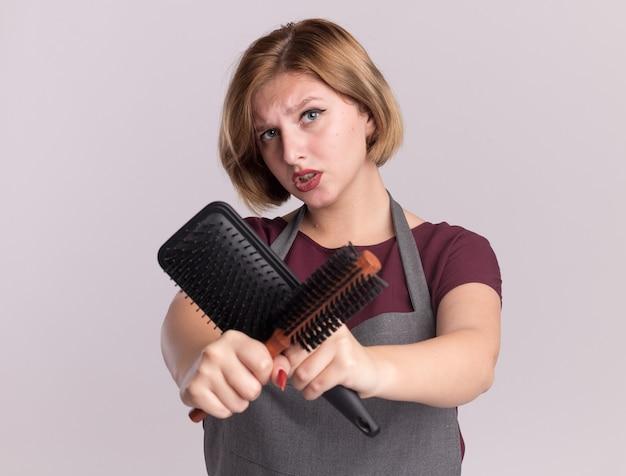 Jonge mooie vrouwenkapper die in schort haarborstels houdt die handen kruisen die voorzijde met ernstig gezicht bekijken die zich over witte muur bevinden