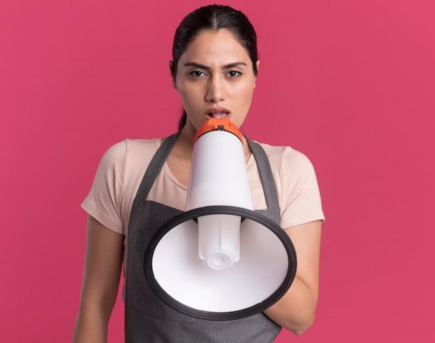 Jonge mooie vrouwenkapper die in schort met megafoon spreekt die voorzijde met ernstig gezicht bekijkt dat zich over roze muur bevindt