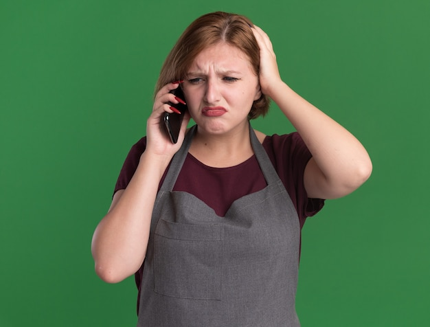 Jonge mooie vrouwenkapper die in schort verward kijkt terwijl het spreken op mobiele telefoon die zich over groene muur bevindt