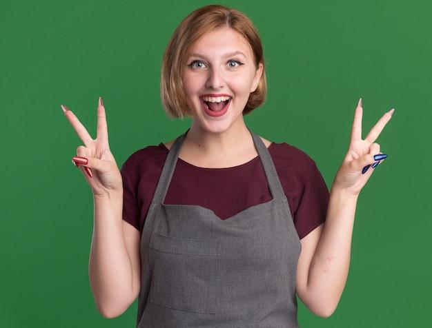 Jonge mooie vrouwenkapper die in schort voorzijde gelukkig en positief bekijken die v-teken tonen die zich over groene muur bevinden