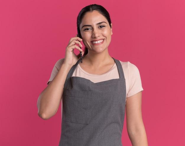 Jonge mooie vrouwenkapper die in schort voorzijde glimlachend met gelukkig gezicht bekijkt terwijl het spreken op mobiele telefoon zich over roze muur bevindt