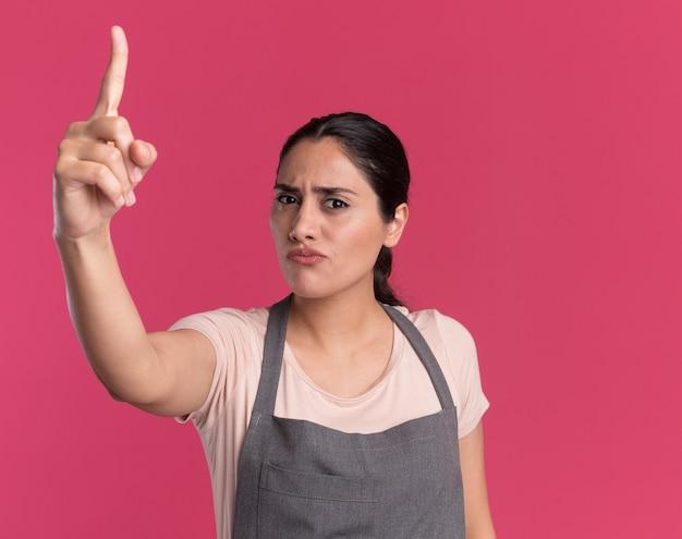 Jonge mooie vrouwenkapper die in schort voorzijde met ernstig gezicht bekijkt dat wijsvingerwaarschuwing toont die zich over roze muur bevindt