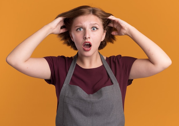 Jonge mooie vrouwenkapper die in schort voorzijde verward en teleurgesteld met handen op haar hoofd bekijkt die zich over oranje muur bevinden