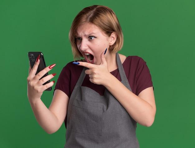 Jonge mooie vrouwenkapper die in smartphone van de schortholding met wijsvinger richt boos en gekke gekke status over groene muur richt