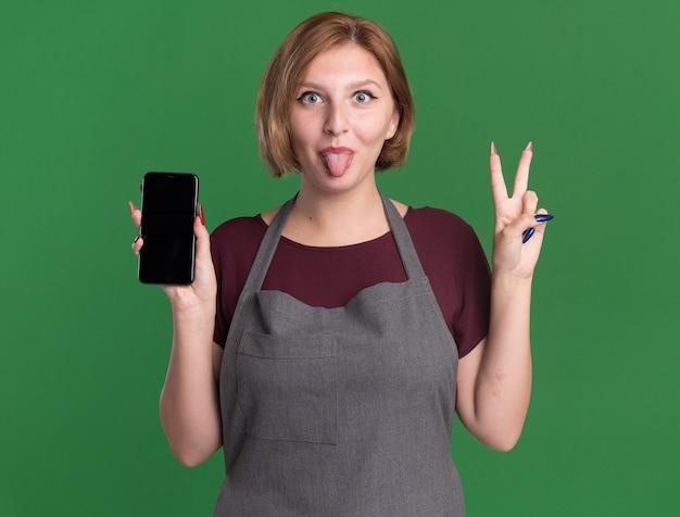 Jonge mooie vrouwenkapper die in smartphone van de schortholding v-teken toont die uit tong gelukkige en positieve status over groene muur steekt