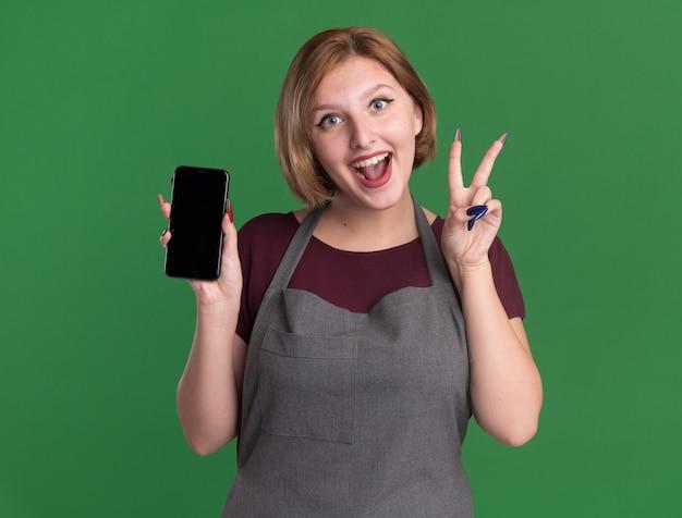 Jonge mooie vrouwenkapper die in smartphone van de schortholding v-teken toont die vrolijk over groene muur glimlacht