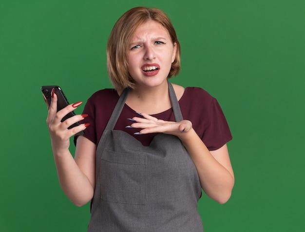 Jonge mooie vrouwenkapper die in smartphone van de schortholding verward en ontevreden voorzijde bekijkt die zich over groene muur bevindt