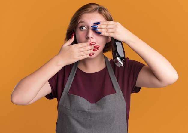 Jonge mooie vrouwenkapper in de trimmer die van de schortholding één oog en mond behandelt met handen die zich over oranje muur bevinden