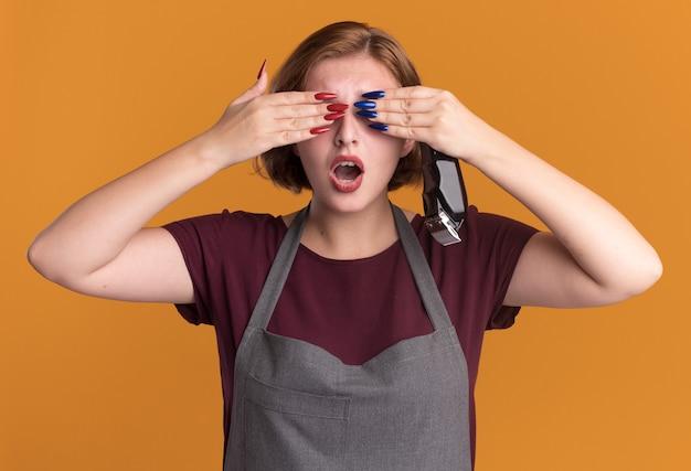 Jonge mooie vrouwenkapper in de trimmer die van de schortholding ogen behandelt met handen die verbaasd status over oranje muur kijken