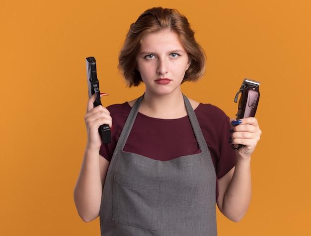 Jonge mooie vrouwenkapper in de trimmermachine en het kanon die van de schortholding voorzijde met ernstig gezicht bekijken die zich over oranje muur bevinden