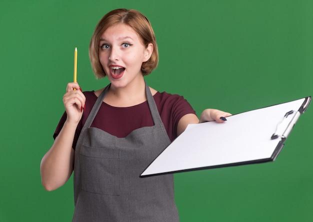 Jonge mooie vrouwenkapper in het potlood dat van de schortholding klembord toont die voorzijde verrast en gelukkig bekijkt met nieuw idee dat zich over groene muur bevindt