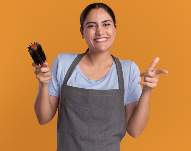 Jonge mooie vrouwenkapper in schort die haarborstel houdt die naar voorkant kijkt lachend met blij gezicht wijzend met wijsvinger aan voorkant staande over oranje muur