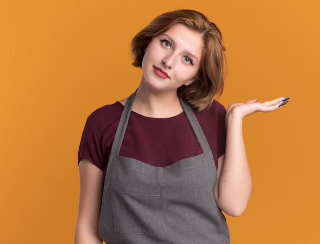Jonge mooie vrouwenkapper in schort die haarborstel houdt die voorzijde met glimlach op gezicht bekijkt die exemplaarruimte presenteert met de arm van haar hand die zich over oranje muur bevindt